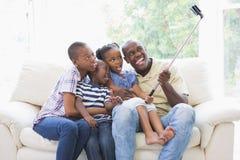 Famille heureuse sur le divan prenant un selfie Images stock