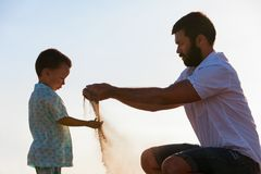 Famille heureuse sur le jeu de plage de mer de coucher du soleil avec le sable Image stock