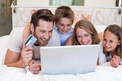Famille heureuse sur le lit utilisant l'ordinateur portable Photos stock
