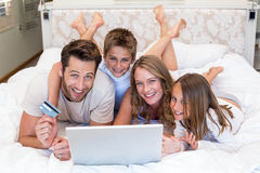 Famille heureuse sur le lit utilisant l'ordinateur portable Image stock