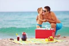 Famille heureuse sur le pique-nique de plage d'été Photographie stock libre de droits