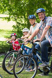 Famille heureuse sur leur vélo au parc Photographie stock libre de droits