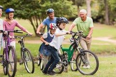 Famille heureuse sur leur vélo au parc Images stock