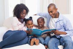 Famille heureuse sur livre de contes de lecture de divan Image libre de droits