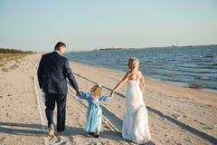 Famille heureuse sur une plage au lever de soleil - mère et père d'enfant photo stock