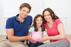 Famille heureuse tenant la tirelire à la maison Images libres de droits