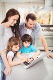 Famille heureuse travaillant sur l'ordinateur portable à la table photos stock