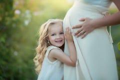 Famille heureuse : une jeune belle femme enceinte avec sa petite fille mignonne marchant dans le domaine orange de blé sur a photos libres de droits