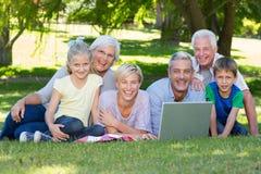 Famille heureuse utilisant l'ordinateur portable en parc Photographie stock libre de droits