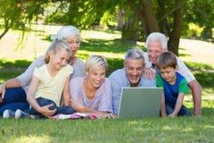 Famille heureuse utilisant l'ordinateur portable en parc Photo stock