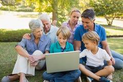 Famille heureuse utilisant l'ordinateur portable en parc Images libres de droits
