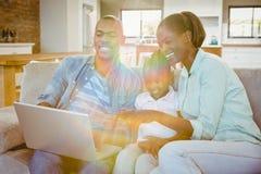 Famille heureuse utilisant l'ordinateur portable sur le divan Images stock