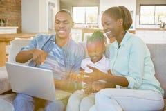 Famille heureuse utilisant l'ordinateur portable sur le divan Photo stock