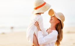 Famille heureux à la plage étreinte de fille de mère et d'enfant au coucher du soleil Photos stock