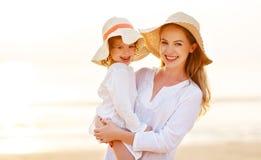 Famille heureux à la plage étreinte de fille de mère et d'enfant au coucher du soleil Photo libre de droits