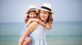 Famille heureux à la plage étreinte de fille de mère et d'enfant en mer image libre de droits