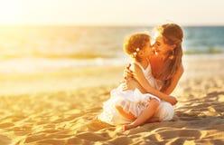 Famille heureux à la plage mère étreignant la fille de bébé au coucher du soleil Photographie stock libre de droits