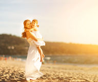 Famille heureux à la plage mère étreignant la fille de bébé au coucher du soleil Image stock