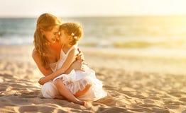 Famille heureux à la plage mère étreignant la fille de bébé au coucher du soleil Photo stock