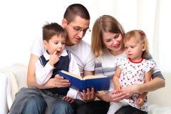 Famille heureux affichant un livre sur le sofa Images libres de droits