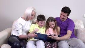 Famille heureux affichant un livre sur le sofa banque de vidéos