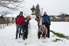 Famille heureux autour d'un bonhomme de neige Image stock