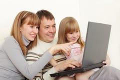 Famille heureux avec l'ordinateur portatif photographie stock