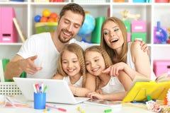 Famille heureux avec l'ordinateur portatif Photographie stock libre de droits