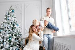 Famille heureux ayant l'amusement à la maison Matin de Noël dans le salon lumineux Jeunes parents avec le petit fils père photographie stock libre de droits