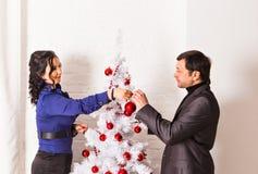 Famille heureux décorant un arbre de Noël Image stock