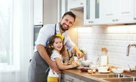 Famille heureux dans la cuisine La fille de père et d'enfant malaxent la pâte a Image stock