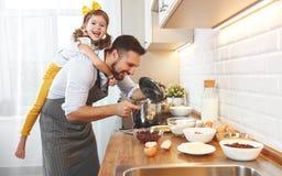 Famille heureux dans la cuisine La fille de père et d'enfant malaxent la pâte a Photo stock