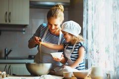 Famille heureux dans la cuisine la mère et l'enfant préparant la pâte, font cuire au four photos stock