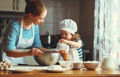 Famille heureux dans la cuisine la mère et l'enfant préparant la pâte, font cuire au four Photographie stock