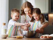 Famille heureux dans la cuisine la m?re et les enfants pr?parant la p?te, font des biscuits cuire au four image libre de droits