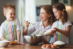 Famille heureux dans la cuisine la m?re et les enfants pr?parant la p?te, font des biscuits cuire au four images stock