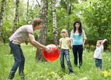 Famille heureux extérieur jouant la bille. Photographie stock