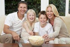 Famille heureux mangeant la télévision de observation de maïs éclaté Photos stock