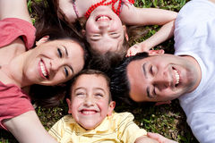 Famille heureux s'étendant en cercle sur l'herbe verte Photos stock