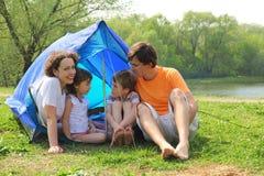 Famille heureux s'asseyant dans la tente sur la pelouse photos libres de droits