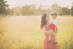 Famille heureux Une mère et un fils jouant dans des domaines d'herbe dehors Photo stock