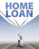 Famille hispanique tirant une bannière de prêt immobilier Images stock
