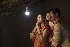 Famille indienne rurale ravie sur l'électricité atteignant leur maison photographie stock libre de droits