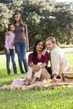 Famille interracial appréciant le pique-nique en stationnement images stock