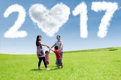 Famille jouant au champ avec le nuage 2017 Photo stock