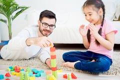 Famille jouant avec des blocs de jouet Images stock