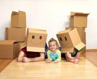 Famille jouant avec des boîtes en carton Photographie stock libre de droits
