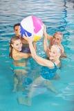 Famille jouant avec la boule de l'eau dans la piscine Images libres de droits