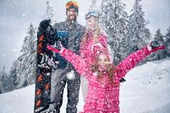 Famille jouant avec la neige extérieure dans le jour ensoleillé sur le mounta de neige Photo stock