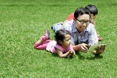 Famille jouant avec la tablette digitale extérieure Photographie stock